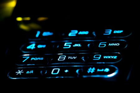 backlit keyboard: Close up view of a cell phone keypad ringing. Use of selective focus.