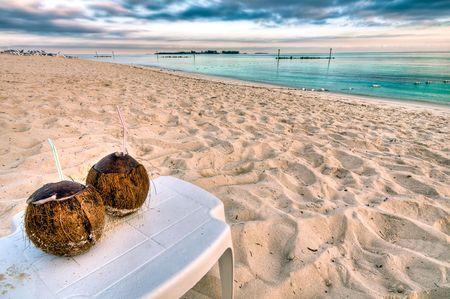 Kokos drinken in een tropisch strand in Nassau, Bahamas bij zons opgang.  Stockfoto