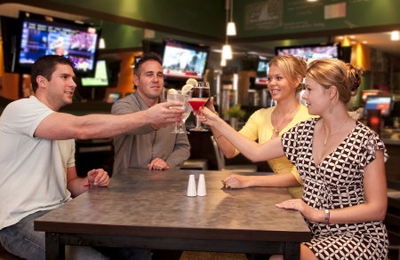 sports bar: Young friends  in a modern bar and lounge toasting.