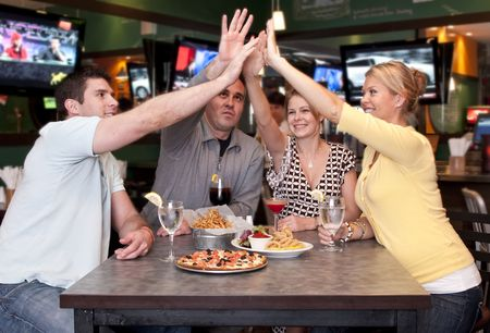 bar: Group of friends having fun in a sport bar and raising hands, very cheerful.