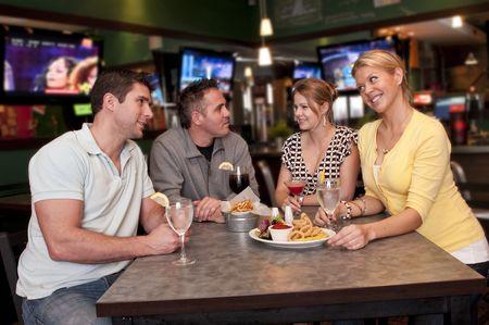 Groep vrienden met een zeer vrolijk in een bar gesprek. Stockfoto