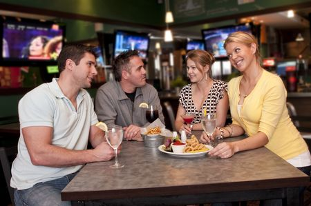 sports bar: Group of friends having a conversation very cheerful in a bar.