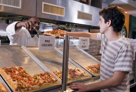 Young guy buys a slice of pizza in a modern restaurant