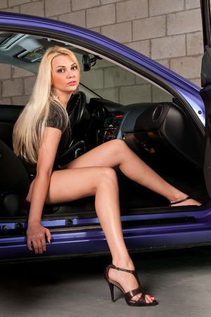 Sensual blond girl getting out of a car in a garage photo