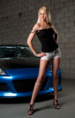 Sensual blond girl stading in front of sport car in a garage. photo