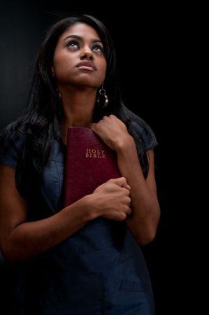 Jonge vrouw kijken zeer trouwe en holding de Bijbel.