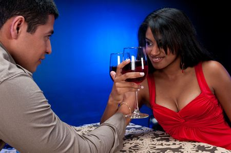Young hispanic couple celebrating and toasting at night club or restaurant setting. photo