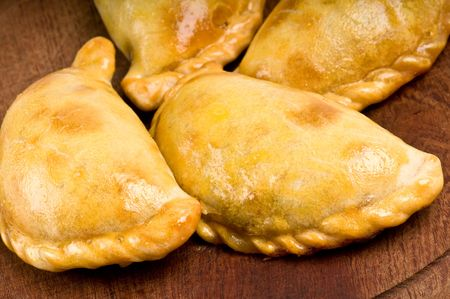 Group of Latin american empanadas. The Empanada is a pastry turnover filled with a variety of savory ingredients and baked or fried. Stock Photo
