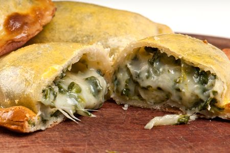 Spinach empanada fill close up.  The Empanada is a pastry turnover filled with a variety of savory ingredients and baked or fried. photo