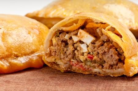 Rindfleisch Empanada Füllung hautnah.  Die Empanada ist eine Konditorei-Umsatz und gebacken oder gebraten mit einer Vielzahl von ausgezeichnete Zutaten gefüllt. Standard-Bild - 6989179