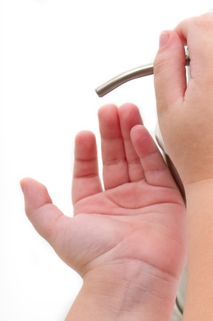 sanitizer: Close up of hand sanitizer being poured into child hands. Isolated on white.