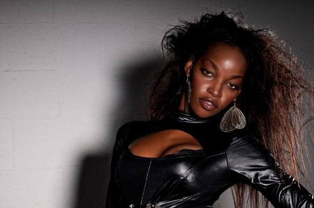 Sensuele African American met leder catsuit poseren.