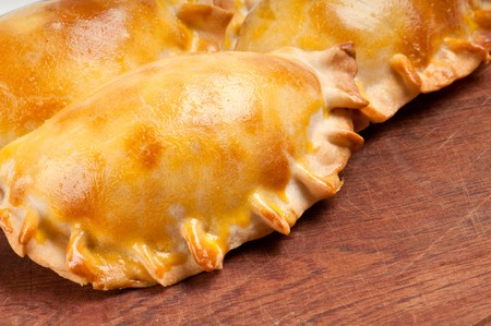 Group of Latin american empanadas over wooden plate. The Empanada is a pastry turnover filled with a variety of savory ingredients and baked or fried. photo