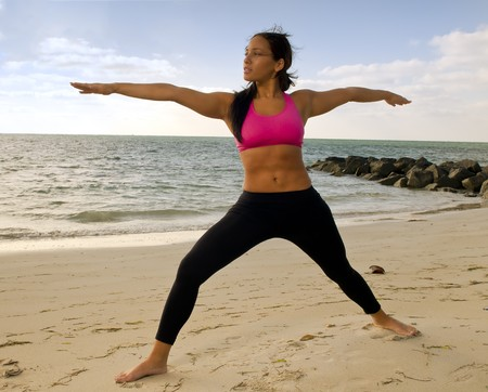 Young woman practices yoga early morning in the beach. Stock Photo - 8025423