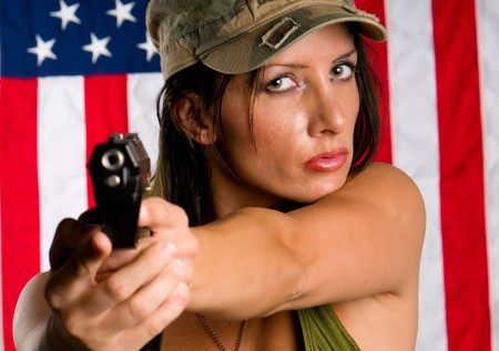 Young woman wearing military uniform pointing with gun. Use of selective focus. Focus in woman. photo