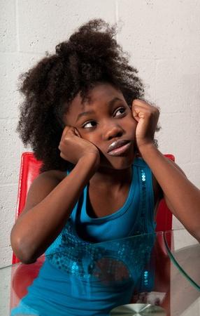 African American girl zitten nadenkend met bezorgd expressie.