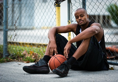 a basketball player: Basketball Player seated in a street.
