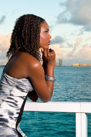 Joven mujer afroamericana medita en una terraza durante la puesta de sol con el océano en segundo plano. Foto de archivo
