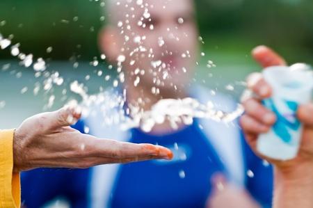 Loper water tijdens een marathon van een vrijwilliger hand te grijpen. Gebruik van selectieve aandacht. Stockfoto