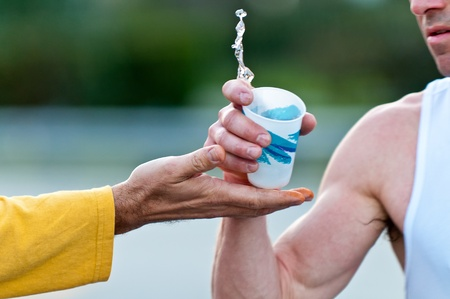 Runner grabbing water during a marathon from a volunteer hand. Use of selective focus. Stock Photo