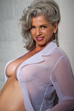 Zeer aantrekkelijke vrouw in haar jaren vijftig poseren met transparante shirt.