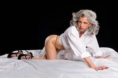 Zeer aantrekkelijke volwassen vrouw speelse in haar beedroom Stockfoto