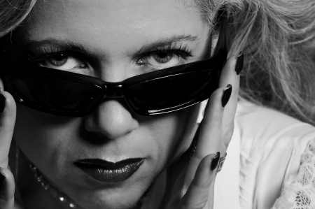 Attractive woman in her fifties looking over sunglasses photo