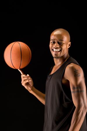 Jonge basketbalspeler met een bal en gelukkig lachend. Stockfoto