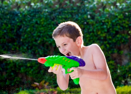 Kid playing with water toy in the summer. Standard-Bild