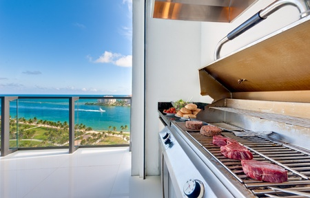 Weergave van een barbecue in een luxe terras met uitzicht op de oceaan.
