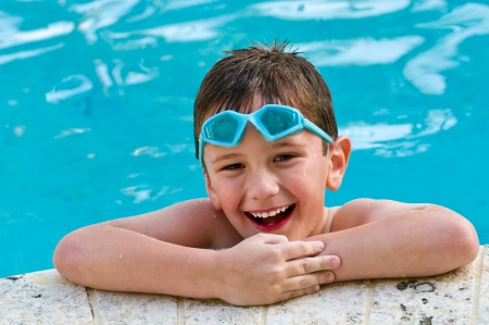 5 year old kid laughing in a swimming pool. Archivio Fotografico