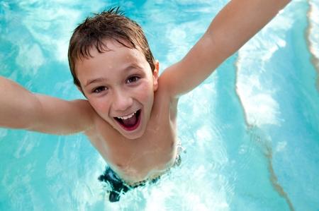 ni�os nadando: Retrato de ni�o muy juguet�n y salto en una piscina.