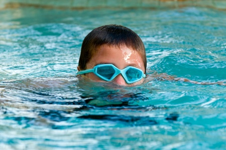 submerging: Child wearing googles and submerging in a swimming pool.