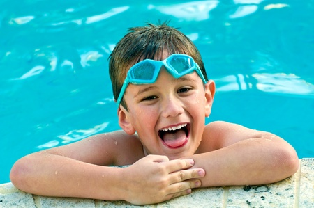 swimming goggles: 5 year old kid enjoying the summer in a swimming pool.