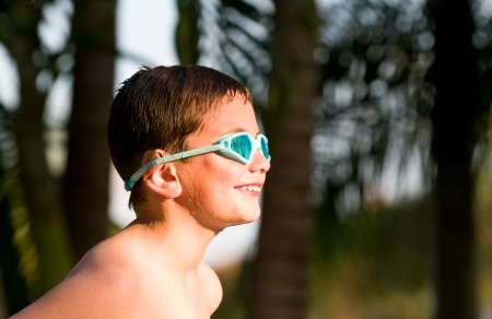 Portrait of a 5 year old kid in the summer with googles and wet. photo