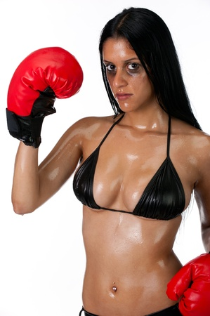 Attractive hispanic woman training with boxing gloves and sweaty. photo