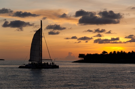 catamaran: Catamaran sailing with tourists with a caribbean island behind at sunset. Stock Photo