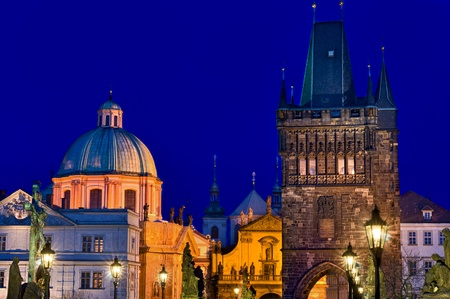View of tower of  the Charles Bridge and Prague skyline at night. photo