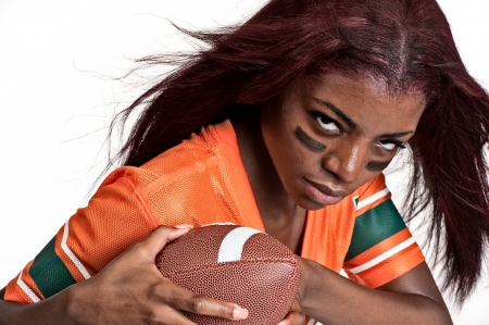 jerseys: Portrait of young woman playing american football. Stock Photo