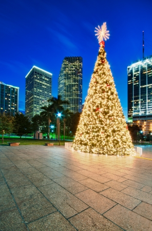 twilight: Christmas tree in Miami Bayfront Park, with cityscape in the back at night. Stock Photo