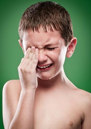 Portret van jongen huilen, handen op het gezicht.