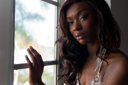 Portret van jonge african american in een venster kijken naar de camera
