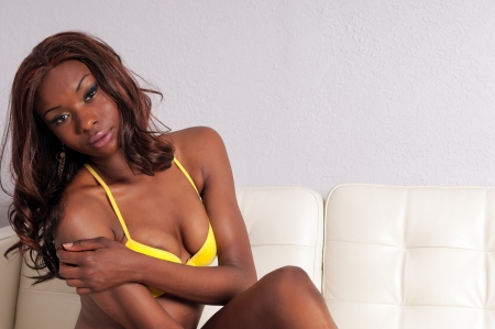 woman on couch: Portrait of young african american woman in lingerie