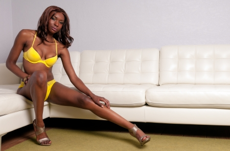 couches: Sensual African American woman seating with lingerie in a couch  Stock Photo