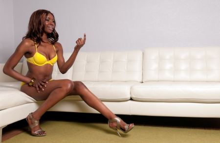 Sensual African American woman seating with lingerie in a couch smiling and calling Stock Photo - 12987673