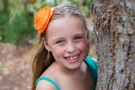 7 9 years: Portrait of happy 8 years old girl outdoors, looking at camera and smiling behind a tree