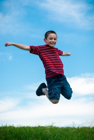 6 years old boy jumping very happy in a park during summertime photo