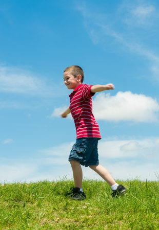 5 6 years: 6 years old boy running with arms extended very happy in a park during summertime