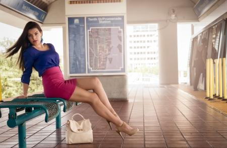 mujeres sentadas: Mujer joven sentada y esperando en un andén de la estación de metro Foto de archivo