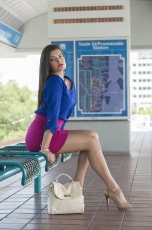 piernas sexys: Mujer joven sentada y esperando en un andén de la estación de metro Foto de archivo